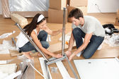 Couple moving in together assembling furniture table — Stock Photo