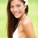 Bikini girl wearing Hawaiian flower smiling fresh — Stock Photo #26073305
