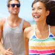 Young happy couple laughing having fun on beach — Stock fotografie