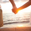 Summer couple holding hands at sunset on beach — Stock Photo