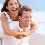 Happy couple piggybacking on beach. — Stock Photo