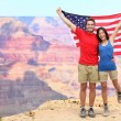 USA travel tourist couple holding american flag — Stock Photo