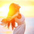 Enjoyment - free happy woman enjoying sunset — Stock Photo #26073829