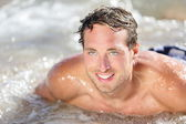 Beach man having fun in water — Stock Photo