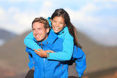 Happy hiking couple piggyback — 图库照片