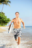 Beach lifestyle - man surfer with surfboard — Stock Photo