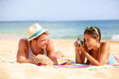 Beach fun couple travel - woman taking photo — Stockfoto