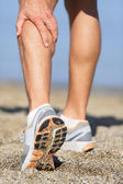Sport injury - Man running clutching calf muscle — Stock Photo