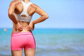 Back pain - Athletic woman rubbing her back — Stok fotoğraf