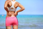 Sırt ağrısı - atletik kadın onu geri ovuşturarak — Stok fotoğraf