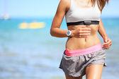 Běžec žena s srdeční frekvence monitoru běží — Stock fotografie