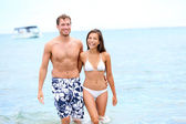Beach couple in love walking happy in water — Stock Photo