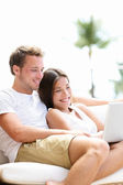 Couple relaxing together in sofa with laptop pc — Stock Photo
