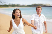 Beach couple running having fun laughing together — Stock Photo