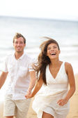 Beach fun - couple laughing and running together — Stock Photo