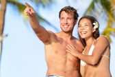Couple on beach happy in swimwear, man pointing — Stock Photo