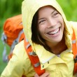 Stock Photo: Happy hiker woman hiking in rain with backpack