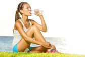 Fitness woman drinking water after workout outside — Stock Photo