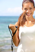 Fitness girl training at beach elastics bands — Stock Photo