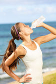 Fitness woman drinking water after beach running — Stock Photo