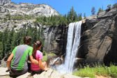 Hikers couple resting in Yosemite park - waterfall — Stock Photo