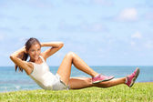 Exercising fitness woman doing sit ups outside — Stock Photo