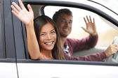 Drivers driving in car waving happy at camera — Stock Photo