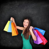 Shopping woman holding shopping bags on blackboard — Stock Photo