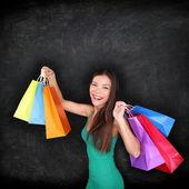 Shopping woman holding shopping bags on blackboard — Stock Photo