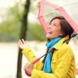 Woman happy with umbrella under the rain — Stock Photo