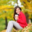 Happy woman drinking coffee in fall forest outdoor — Stock Photo #28788587