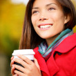 Autumn woman drinking coffee in fall city park — Stock fotografie