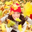 Autumn woman happy with colorful fall leaves — Stockfoto