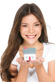 Buying new home concept - woman holding mini house — Stock Photo