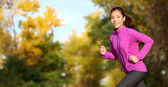 Female runner running in fall forest outside — Stock Photo