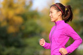 Asian woman running in autumn forest in fall — Stock Photo