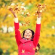 Stock Photo: Autumn, fall womhappy throwing leaves