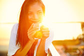 Asian woman drinking coffee in sun — Stock Photo