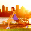Woman runner stretching legs after running — Stock Photo
