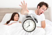 Wake up - couple waking up early throwing alarm — Stock Photo