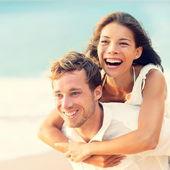 Love - Happy couple on beach having fun piggyback — Stock Photo