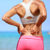 Back pain - woman having injury in lower back — Stok fotoğraf