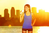 Fitness runner drinking water after city running — Stock Photo