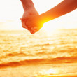 Love - couple holding hands in love, beach sunset — Stock Photo