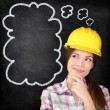 Thinking construction worker girl on chalkboard — Stock Photo