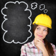 Stock Photo: Thinking construction worker girl on chalkboard