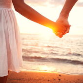 Love - romantic couple holding hands, beach sunset — Stock Photo