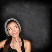 Thinking woman by blackboard — Stock Photo