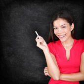 Teacher woman holding chalk by blackboard — Stock Photo