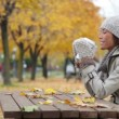 Fall woman sitting in autumn park drinking coffee — Stock Video